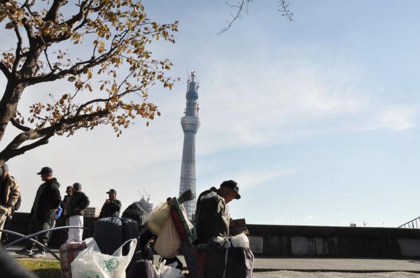 スカイツリーの威容と炊き出しを待つ山谷の路上生活者。(31日、墨田公園。写真:筆者撮影)