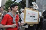 真っ赤なシャツにパーカション。祭り気分に湧く抗議集会だ。(14日、東電本店前。 写真:筆者撮影)