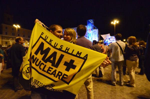 「ネバー・フクシマ」の大フラッグを見せるカップル。(現地時間10日夜、ポポロ広場。 写真:筆者撮影)