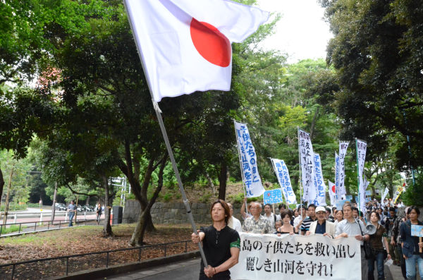 日章旗を先頭に進むデモ隊。横断幕の右端を持つのが鈴木邦男・一水会顧問。(31日、芝公園前。写真:筆者撮影)