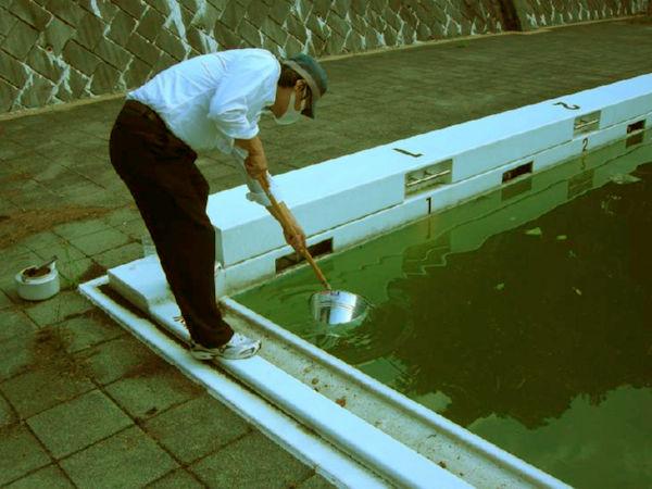 プールのたまり水を採取する川根眞也さん。(埼玉県内の中学校で。写真:川根氏提供)