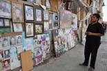 先月16日、戦士した友人の遺影を探す男性。「死ぬ2日前まで一緒だった。とても悲しい」。(27日、サーヘッド・アル・タハリール広場。写真:筆者撮影)