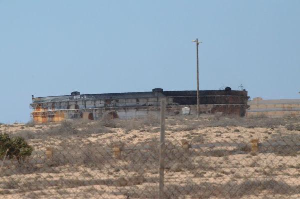 カダフィ軍が火を放った石油貯蔵タンク。反政府軍兵士によれば施設の周囲には地雷が敷設されている。筆者はアスファルト道路から外に出ないようにしてカメラのシャッターを切った。(石油積み出し港ブレガー。写真:筆者撮影)