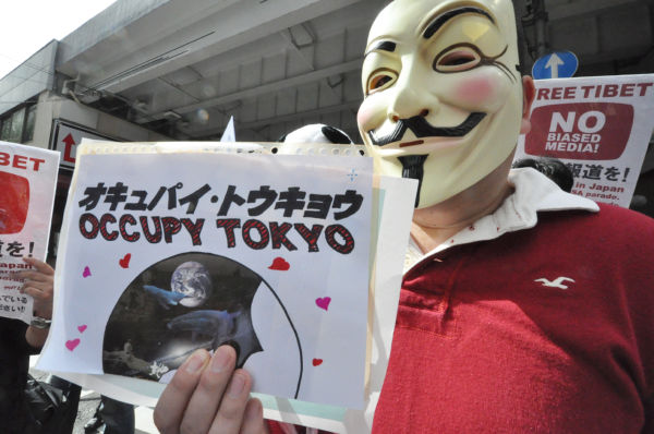 アラブの春で重要な役割を果たし、ウォール街でも活躍するネット集団「アノニマス」のマスクを被った参加者。(内幸町~日比谷公園からのデモ。写真:筆者撮影)