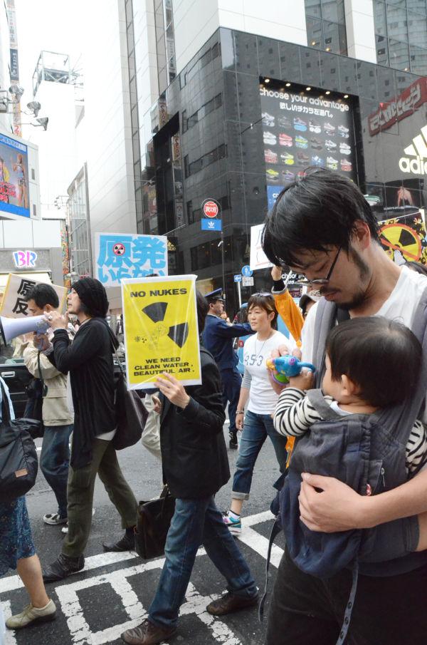 乳飲み児を抱いた父親。日常の風景が混じるようになった脱原発パレード。(同日、渋谷。写真:筆者撮影)