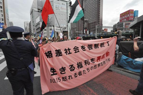 貧困は今や世界共通のテーマだ。パレスチナの旗(右)を掲げる参加者もいた。(15日、新宿西口。写真:筆者撮影)