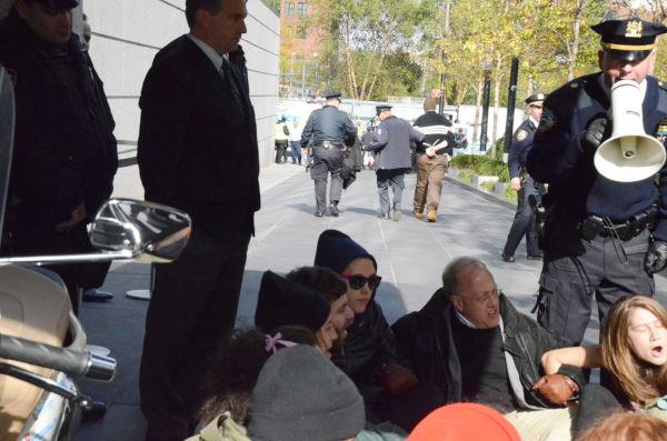 逮捕を覚悟で抗議の座り込みをするクリス・ヘッジズ記者(拡声器を持った警察官の左隣)。=3日(現地時間)、ゴールドマン・サックスが入居するビルの玄関前。写真:筆者撮影=