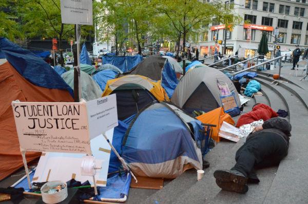 ステューデントローンの負担の大きさに抗議するプラカード。横にはテントからあぶれ寝袋にくるまる占拠者=ズコッティ公園。写真:筆者撮影=