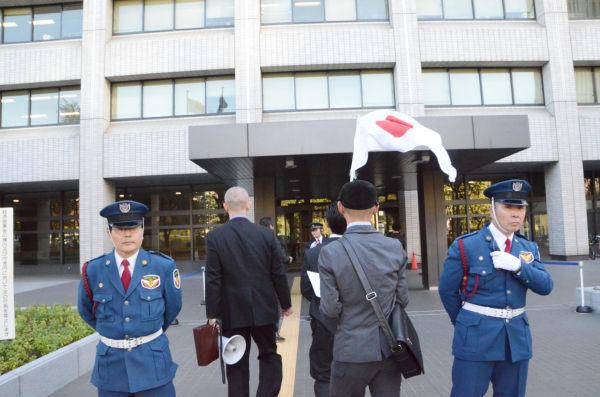 枝野大臣あての要請書を手渡すため、日の丸を翻して経産省に入る「統一戦線義勇軍」の一行。=16日朝、経産省。写真:筆者撮影=