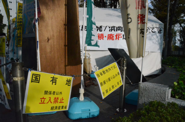 12日昼前、警察官40人が警護するなか経産省は鎖を張り巡らしプラカードをかけた。=12日、経産省前。写真:筆者撮影=