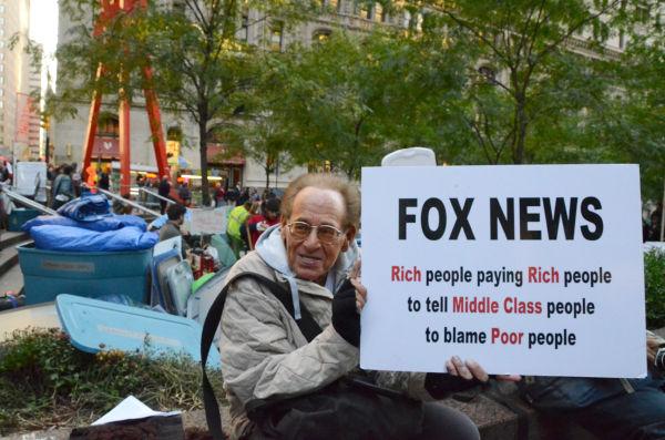 体温を奪い尽くすかのような冬のビル風が吹付けるなか、老人はフォックステレビを批判するプラカードを手に座り続けていた。=ズコッティ公園。写真:筆者撮影=