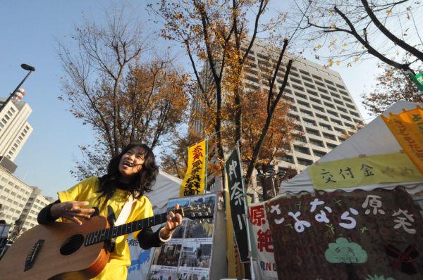 経産省の巨大ビルを背に美声を披露する早苗NENEさん。原子力村の幹部たちにもやさしく歌いかけるようだった。=15日、霞が関。写真:筆者撮影=