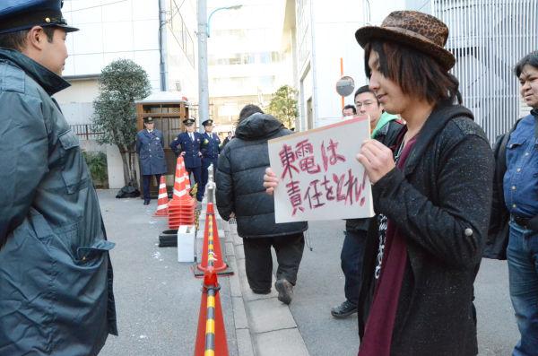 勝俣会長邸前でプラカードを手に抗議の声を挙げる山口さん。=31日午後、新宿区左門町。写真:中野博子撮影=