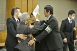 脱原発運動家が班目委員長に詰め寄ろうとしたが、安全委員会の事務方に制止された。=23日午後、内閣府。写真:筆者撮影=