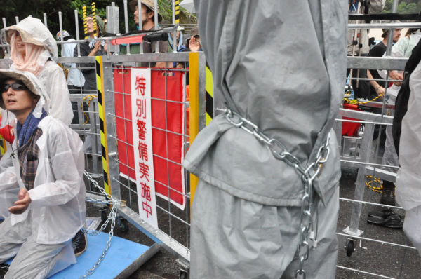反対派はチェーンで自分の体と鉄柵をつないだ。=写真:田中撮影=