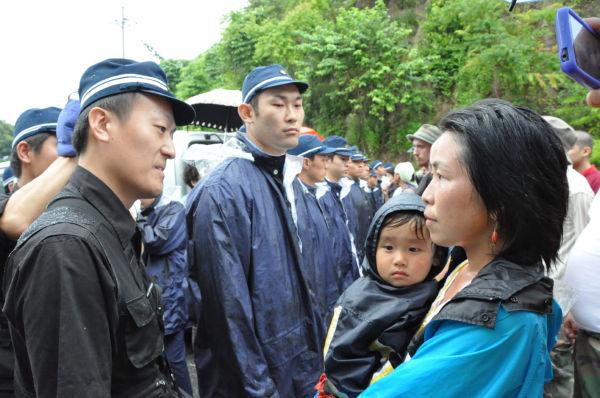母親は「あなたたちは危ない原発の再稼働をなぜ許すのですか?」と言って警察官をニラミつけた。=30日夕、大飯原発入口。写真:田中撮影=