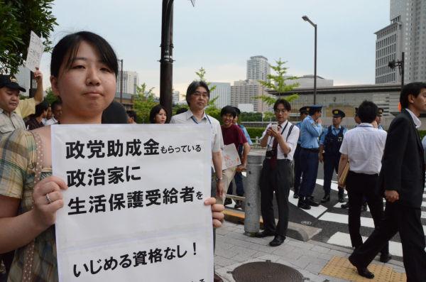 「金曜日の再稼働反対集会に影響された」と話す女性。後方は首相官邸。=18日夕、永田町。写真:田中撮影=