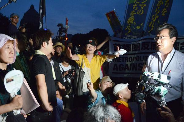「民主党が再稼働させたんでないの!」。川内博史衆院議員(右)に詰め寄る福島県富岡町出身の女性。中央の男性(黄色シャツ)は制止するスタッフ。=29日午後7時頃、国会議事堂前。写真:田中撮影=