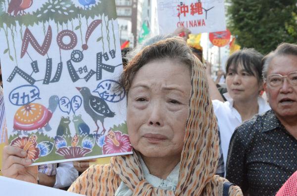 米軍基地のために先祖代々の土地を提供させられたという沖縄出身の女性は、涙を流しながらデモ行進した。=5日、千代田区。写真:諏訪撮影=