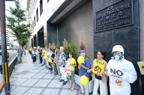 黄色い風船を持った市民たちで包囲された関電京都支店。(写真:田中撮影)