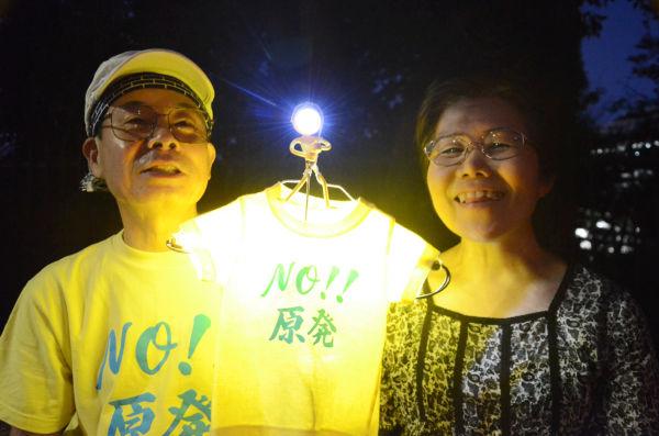 横浜市から訪れた老夫婦が製作したTシャツは、孫と同じサイズ。スイッチオンにするとLED電球に灯りがともり『NO 原発』の文字が浮かびあがった。=3日夕、国会議事堂前。写真:諏訪撮影=
