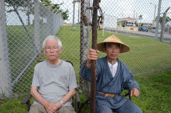 上原成信さん(85歳・左)と小橋川共行さん(69歳・右)。2人は今月、オスプレイ配備反対集会で知り合ったばかりだ。=16日夕、キャンプ・フォスター前。写真:田中撮影=