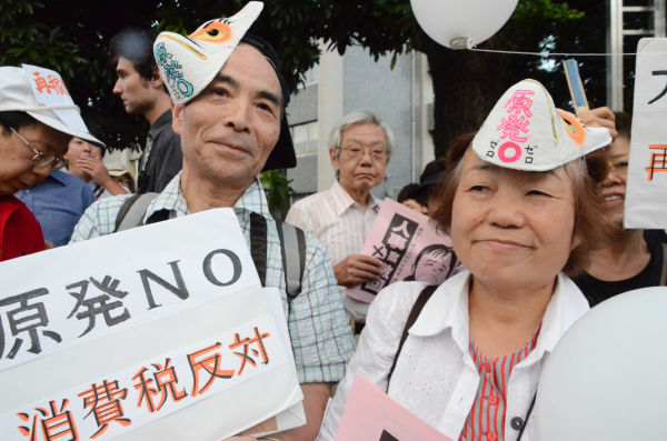 二人は東京北区からきた俳句仲間。「(原発事故で)怒っているはずの動物にかわって、狐のお面をつけて来た」。=官邸前。写真:諏訪撮影=