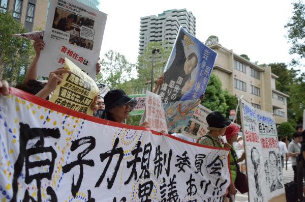 原子力規制庁が入るビルの前では市民たちが「人事の撤回」を求めて声をあげた。=六本木。写真:諏訪撮影=