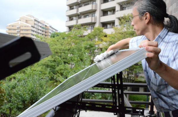 発電効率が下がらないようパネルの汚れを取る。「 本当はもう少し外に出して、日光を確保したいが、規約上、手すりより外には出せない」。マンションならではの不自由もある。 =横浜市。写真:諏訪撮影=