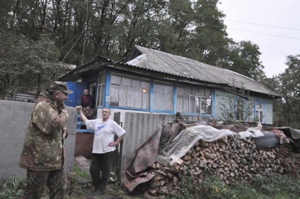 家の外には薪が山積みされていた。「薪割りは重労働だよ」とヴラジミールさんは苦笑いした。隣の男性は国家非常事態省の出先機関「チェルノブイリ・スペッツ・コンビナール」のガイド。=写真:諏訪撮影=
