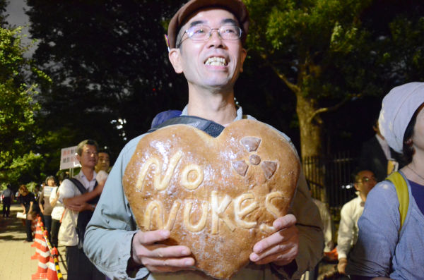 """秩父のパン店経営者(40代)は、小麦を北海道から仕入れている。「再び原発事故が起きればもうパンは作れなくなる」。""""No Nukes パン""""は、お手製だ。=国会議事堂前。写真:諏訪撮影="""