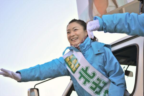 有権者に手を振る北出候補。車から身を乗り出して若さを強調した。=13日朝8時、JR函館駅前。写真:島崎ろでぃ撮影=