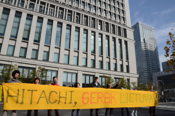 「日立はリトアニアを尊重せよ」。リトアニア語で書かれた横断幕を広げる参加者たち。後ろが日立本社ビル。=写真:田中撮影=