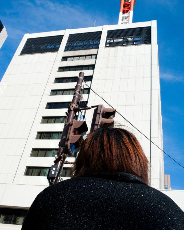 巨大な東電ビル前に向かい一人座って抗議する。=写真:島崎ろでぃ=