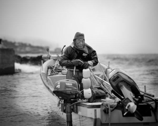 晴天であれば漁師の背中には大間が見える。=13日、函館市戸井。写真:島崎ろでぃ撮影=