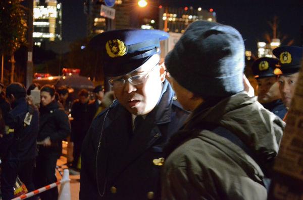 「どいてくれ」と抗議するカメラマン(右)。警察官は「歩道を確保しなければならない」と言って聞き入れなかった。=写真:諏訪都撮影=