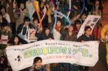 デモが始まると続々と参加する若者が増えていった。安倍首相とヒトラーの合成写真(横断幕のすぐ後ろ)が人目を引いた。=13日夕、渋谷。写真:島崎ろでぃ撮影=