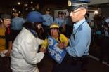 警察からゴボウ抜きにされる女性。参加者から怒号があがった。=25日午後7時45分、公明党本部そば 写真:筆者=
