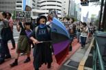 新宿で反戦を訴え続ける大木晴子さんは七色のパラソルを振りながら沿道の人々にアピールした。=5日、靖国通り 写真:田中=